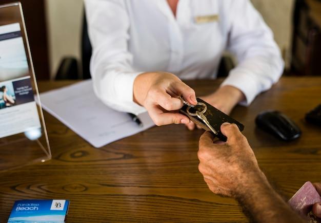 Receptionist che fornisce la chiave della stanza ad un cliente