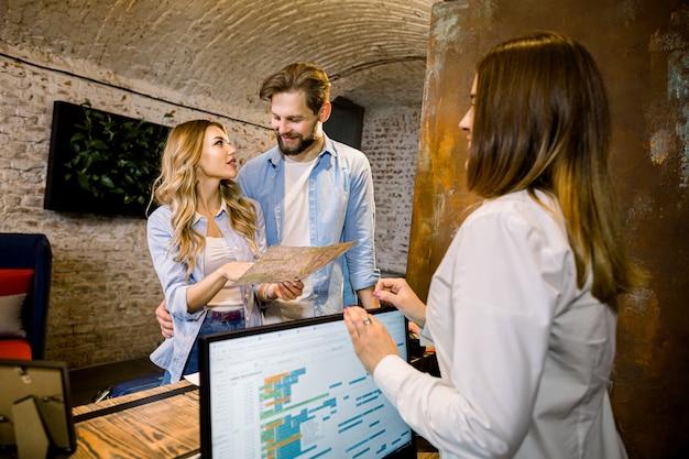 Receptionist femminile che fornisce informazioni turistiche a giovani coppie felici, tenendo la mappa della città, in piedi presso la reception dell'hotel