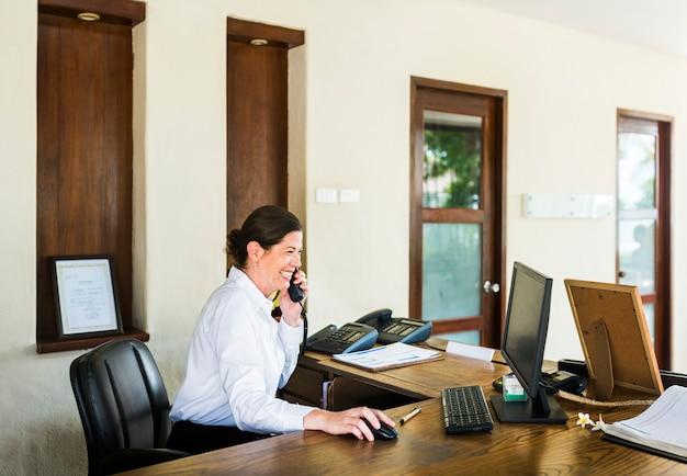 Receptionist femminile del ricorso che lavora alla reception