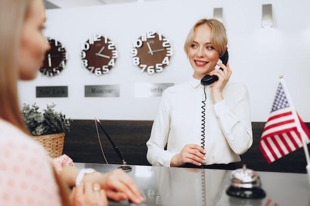 Receptionist femminile in hotel parlando al telefono al lavoro