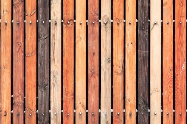 Recinzione in legno rustico realizzata con pannelli di colore diverso trattati. parete verticale del fondo fatta di legno di pino d'annata nello stile d'annata.