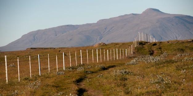 Recinzione metallica scomparsa a distanza attraverso pascoli asciutti fino alla montagna