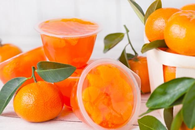 Recipienti di plastica con gelatina di mandarino di mandarino con frutta fresca in scatola di legno su fondo di legno leggero