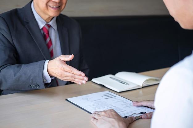 Reclutatore che detiene la lettura di un curriculum durante il colloquio sul suo profilo di candidato