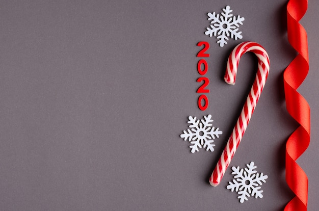 Red stiped candy, numero 2020, nastro e fiocchi di neve bianchi composizione su sfondo scuro, vacanze di natale e capodanno.