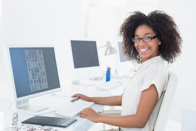 Redattore casuale sorridente che lavora allo scrittorio