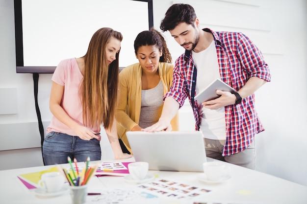 Redattori che utilizzano computer portatile e compressa digitale all'ufficio creativo
