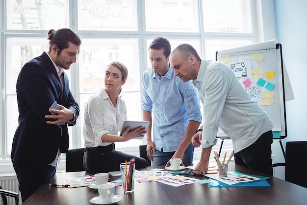 Redattori con documenti e tavoletta digitale che discutono nella sala riunioni