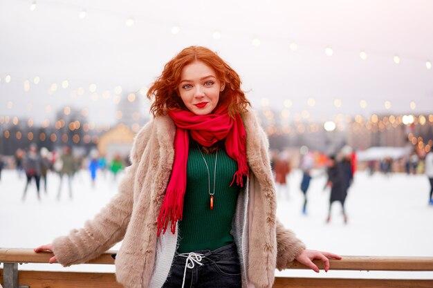 Redhead giovane donna in piedi vicino anello di pattinaggio su ghiaccio tempo di vacanze invernali
