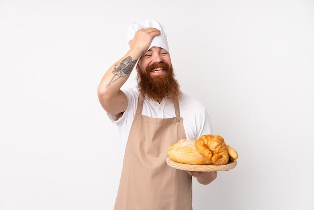 Redhead in uniforme da chef. il fornaio maschio che tiene un tavolo con diversi pani ha realizzato qualcosa e ha inteso la soluzione