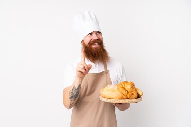 Redhead in uniforme da chef. panettiere maschio che tiene un tavolo con diversi pani con l'intenzione di realizzare la soluzione sollevando un dito
