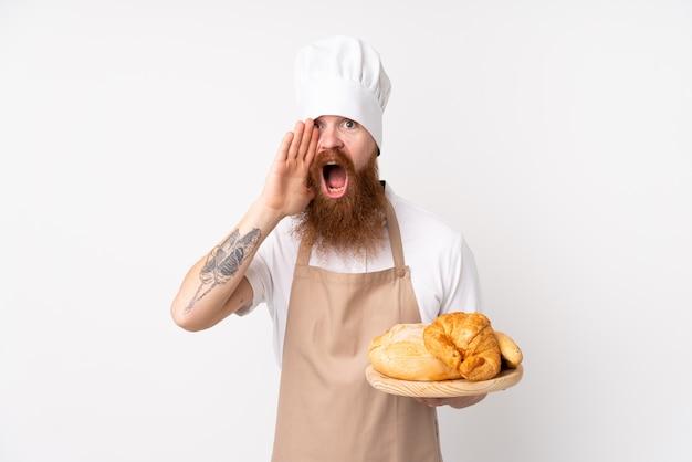 Redhead in uniforme da chef. panettiere maschio che tiene una tabella con parecchi pani che grida con la bocca spalancata