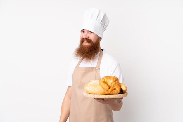 Redhead in uniforme da chef. panettiere maschio che tiene una tabella con parecchi pani con l'espressione felice