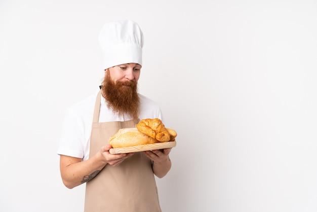 Redhead in uniforme da chef. panettiere maschio che tiene una tabella con parecchi pani