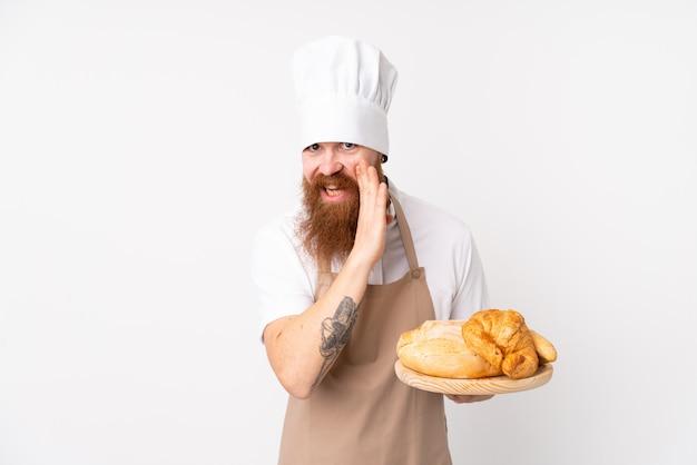 Redhead in uniforme da chef. panettiere maschio che tiene una tavola con parecchi pani che bisbigliano qualcosa