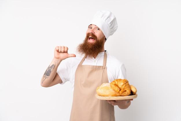 Redhead in uniforme da chef. panettiere maschio che tiene una tavola con parecchi pani fieri e soddisfatti
