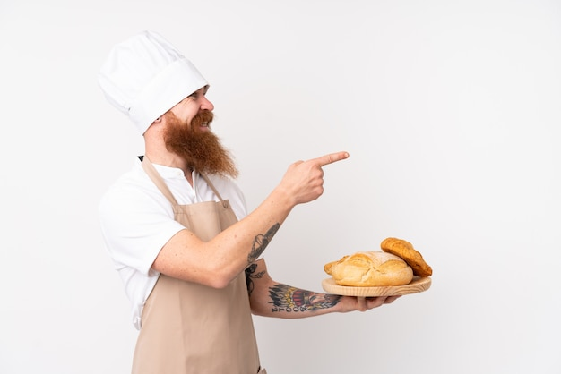 Redhead in uniforme da chef. panettiere maschio in possesso di un tavolo con diversi pani che punta verso il lato per presentare un prodotto