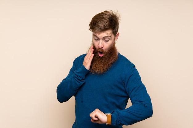 Redhead uomo con la barba lunga con orologio da polso e sorpreso