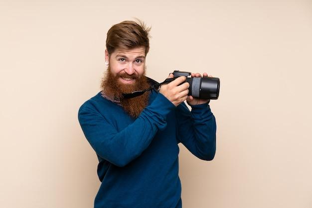 Redhead uomo con la barba lunga con una macchina fotografica professionale