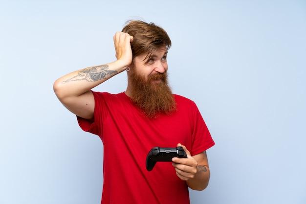 Redhead uomo con la barba lunga, giocando con un controller di videogiochi con dubbi e con espressione del viso confuso
