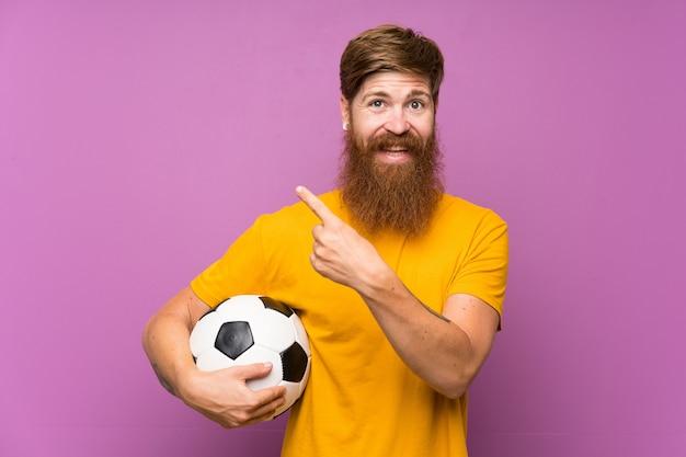 Redhead uomo con la barba lunga in possesso di un pallone da calcio sul muro viola che punta verso il lato per presentare un prodotto