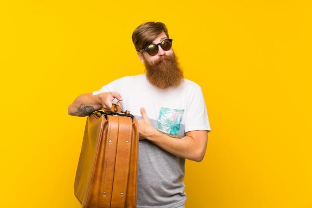 Redhead uomo con la barba lunga in possesso di una valigetta vintage facendo dubbi gesto mentre si sollevano le spalle