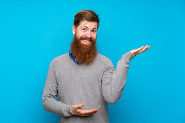 Redhead uomo con la barba lunga sopra isolato blu allungando le mani al lato per invitare a venire