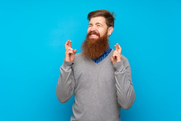 Redhead uomo con la barba lunga sopra isolato blu con le dita che attraversano e desiderano il meglio