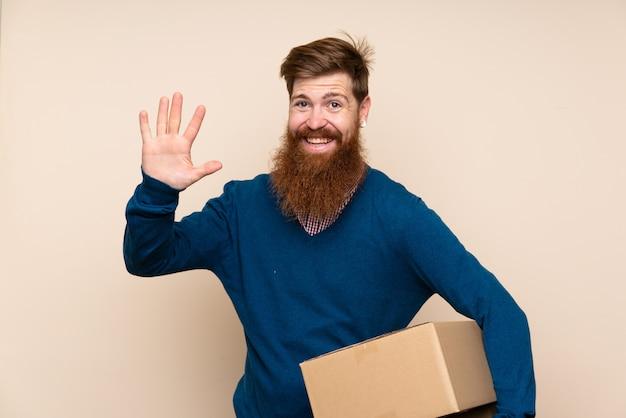 Redhead uomo con la barba lunga sopra isolato in possesso di una scatola per spostarlo in un altro sito e salutare