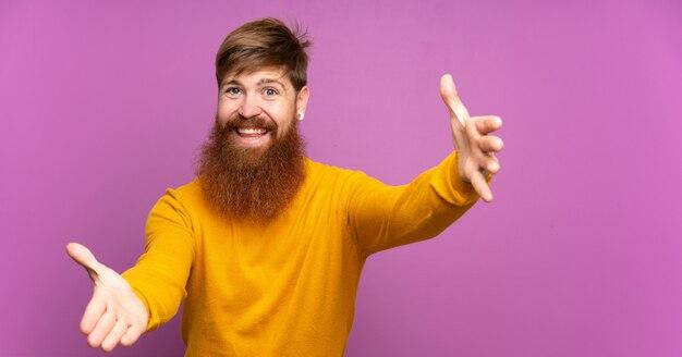Redhead uomo con la barba lunga su viola isolato presentando e invitando a venire con la mano