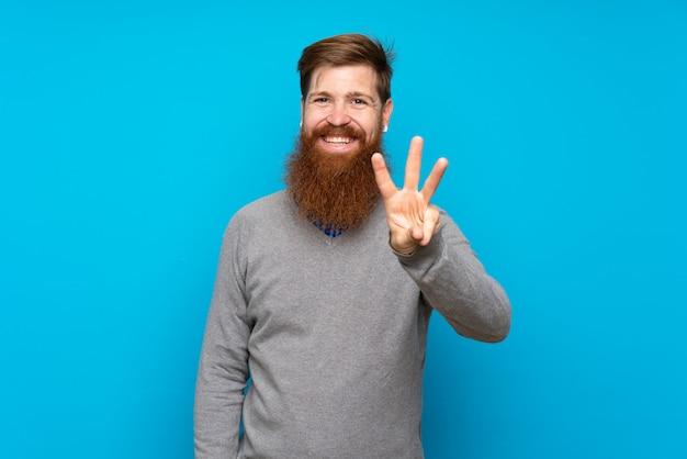 Redhead uomo con la barba lunga sul muro blu felice e contando tre con le dita