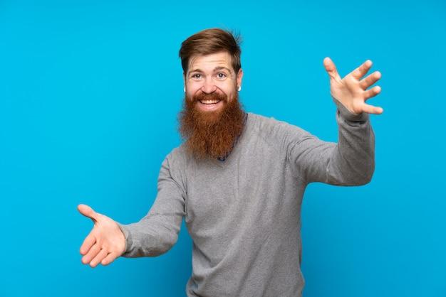 Redhead uomo con la barba lunga sul muro blu presentando e invitando a venire con la mano