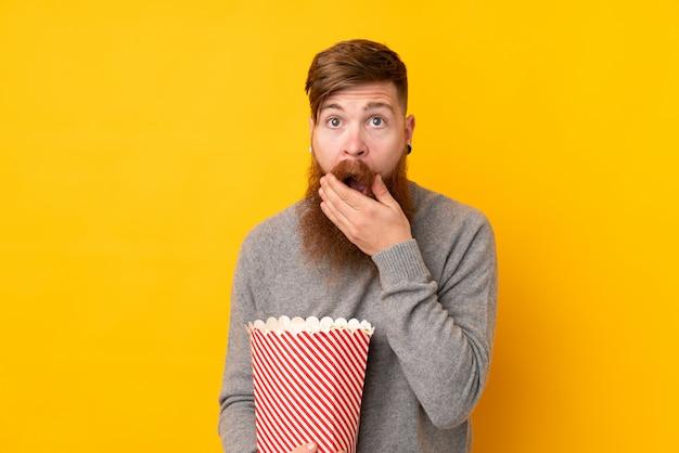 Redhead uomo con la barba lunga sul muro giallo isolato in possesso di un grande secchio di popcorn