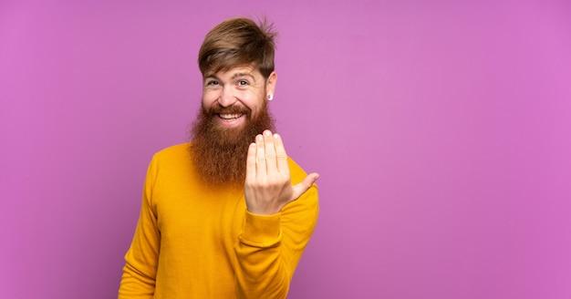 Redhead uomo con la barba lunga sul muro viola che invita a venire con la mano