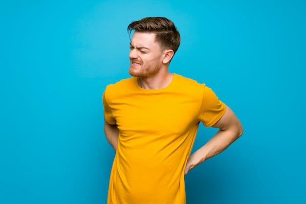 Redhead uomo sopra muro blu soffre di mal di schiena per aver fatto uno sforzo