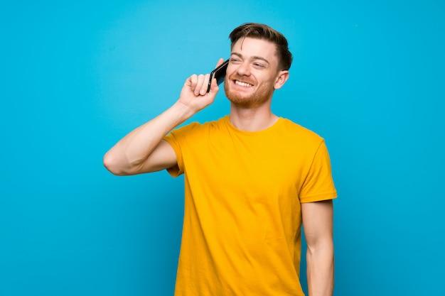 Redhead uomo sul muro blu mantenendo una conversazione con il telefono cellulare