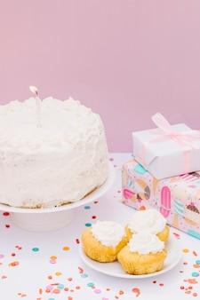 Regali avvolti; cupcake e torta con candela per il compleanno su sfondo rosa