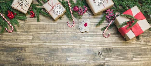 Regali, bacche di agrifoglio e decorazione su tavola di legno.