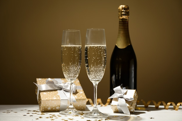 Regali, bicchieri di champagne e bottiglia su spazio dorato, spazio per il testo