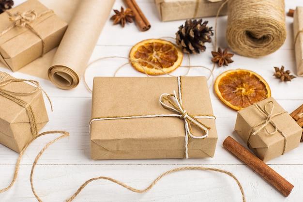 Regali da carta artigianale, arancia essiccata, cannella, pigne, anice su un tavolo bianco