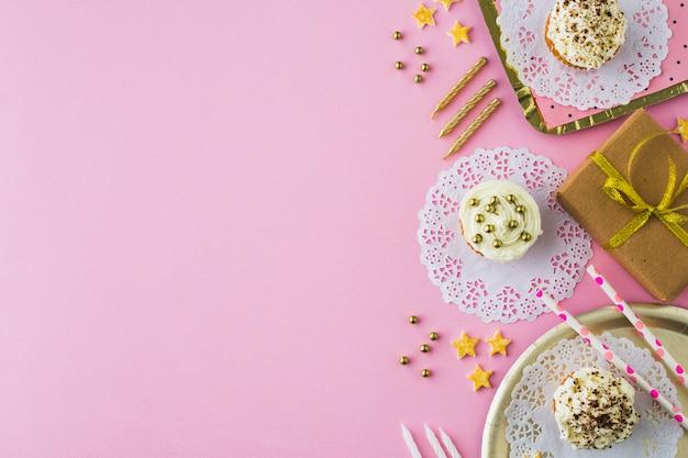 Regali di compleanno; cupcake e candele su sfondo rosa