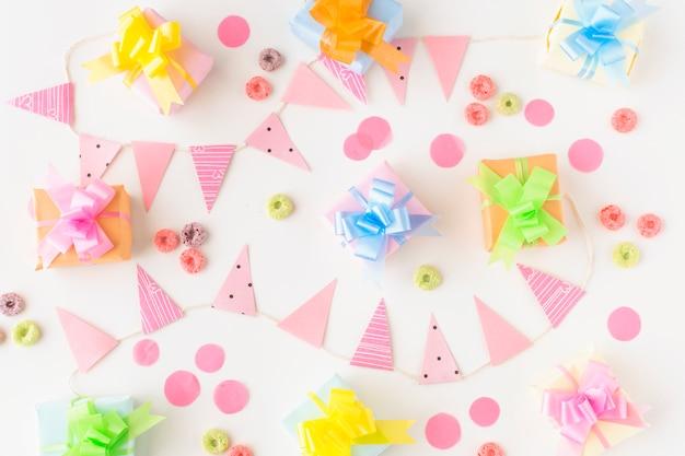 Regali di compleanno; le caramelle dei cerchi di froot e gli accessori del partito su fondo bianco