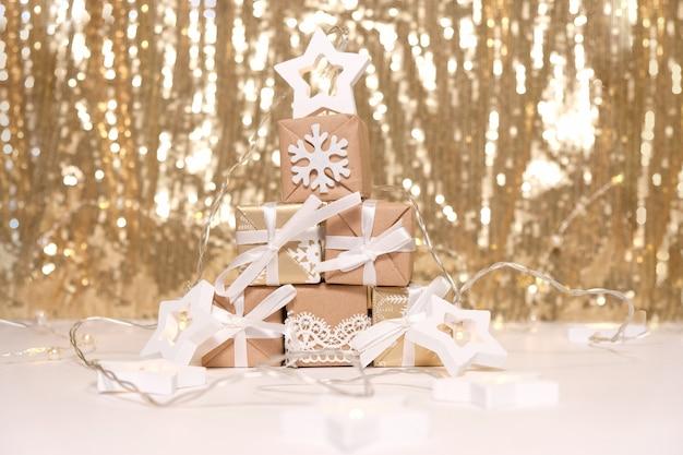 Regali di natale a forma di albero di natale con stella bianca e fiocco di neve