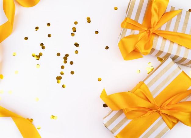 Regali di natale avvolti in carta bianca e oro, coriandoli e un nastro dorato vista dall'alto
