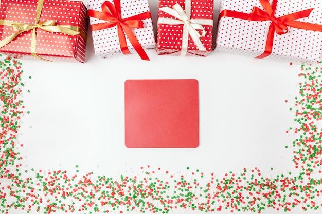 Regali di natale con nastri, carta a forma di quadrato rosso e scintillii su bianco