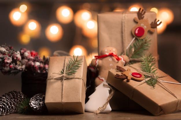 Regali di natale con scatole, conifere, cestino, coni di canna di caramella su fondo di legno