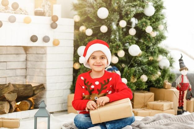 Regali di natale di apertura del ragazzino felice vicino all'albero di capodanno