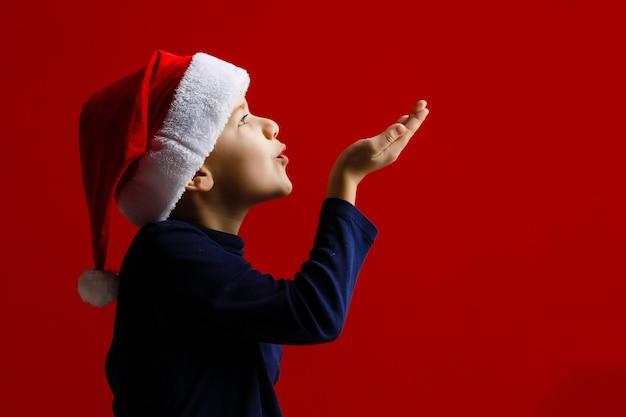 Regali di natale felici della holding del bambino su una priorità bassa rossa