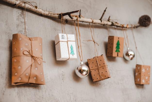 Regali di natale imballati con carta kraft e decorazioni fatte a mano appese a una corda legata a un bastone contro un muro di cemento grigio.