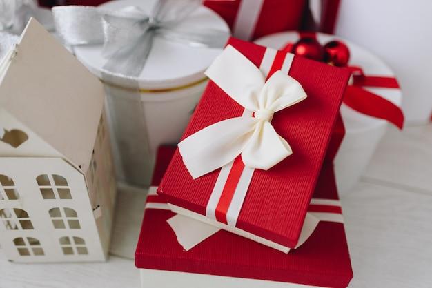 Regali di natale in scatole rosse e bianche con nastri